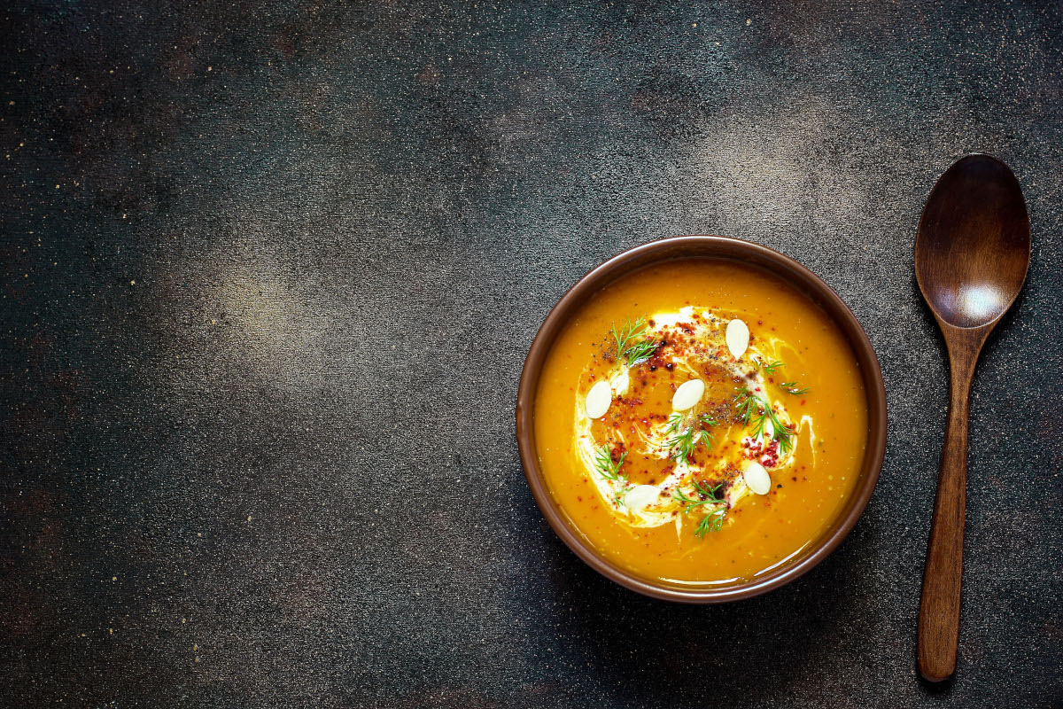 Roasted pumpkin and carrot soup with cream, seeds and fresh gree